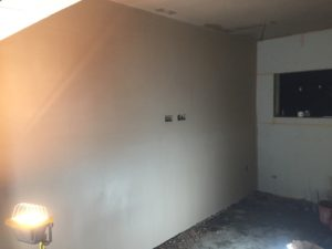 project for plasterer in didsbury - image shows hand holding trowel on wall